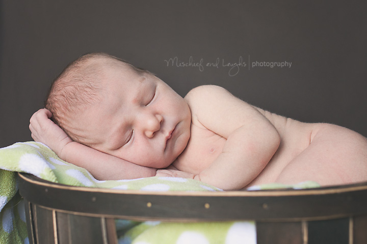 Newborn baby sleeping on a green blanket