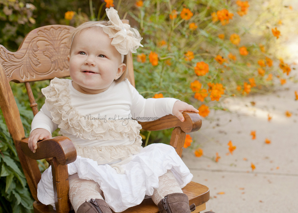 one year old baby sits in a heirloom rocking chair