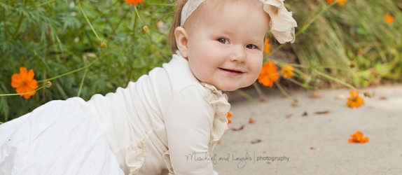 baby girl crawling near orange flowers
