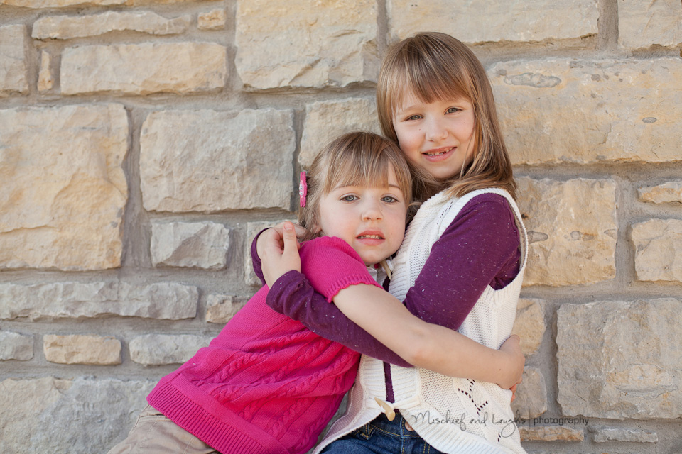 sisters hug each other during their photo session