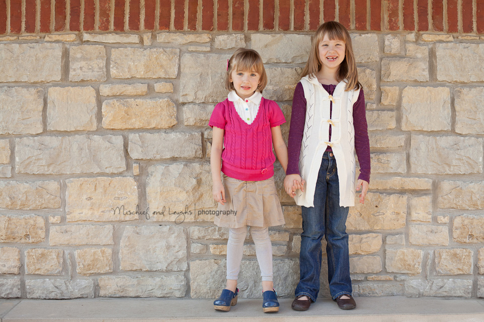 children holding hands and giggling next to a stone wall