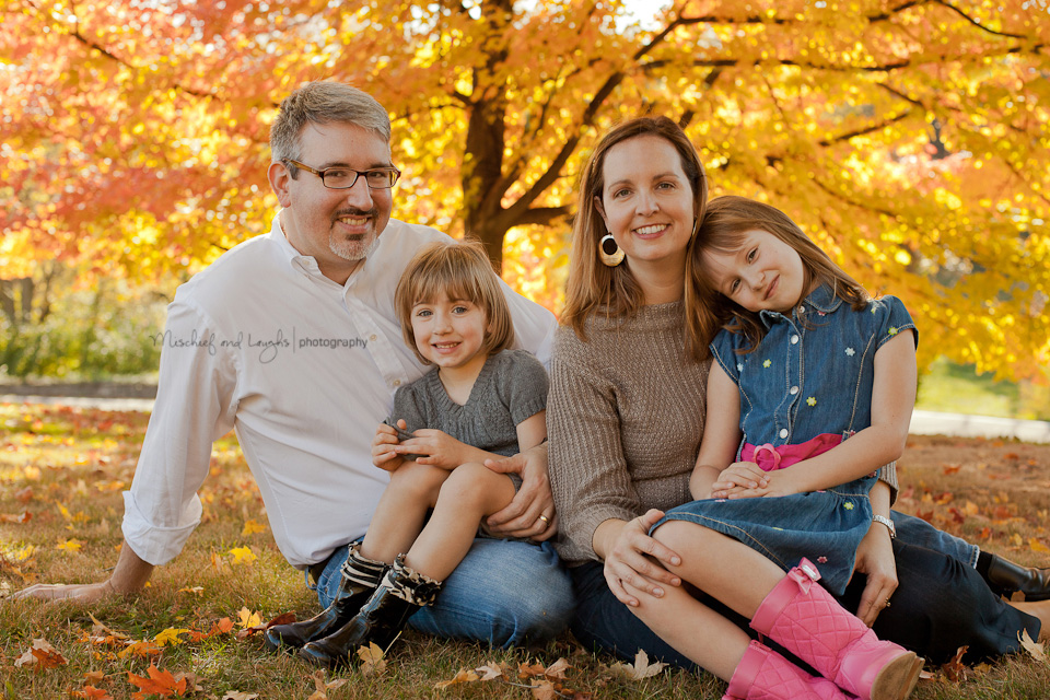 fall family portraits in the middle of the yellow leaves