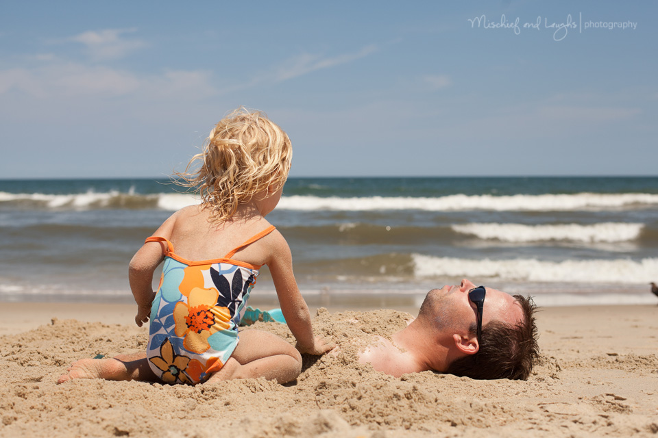 little girl burying her daddy in the sand