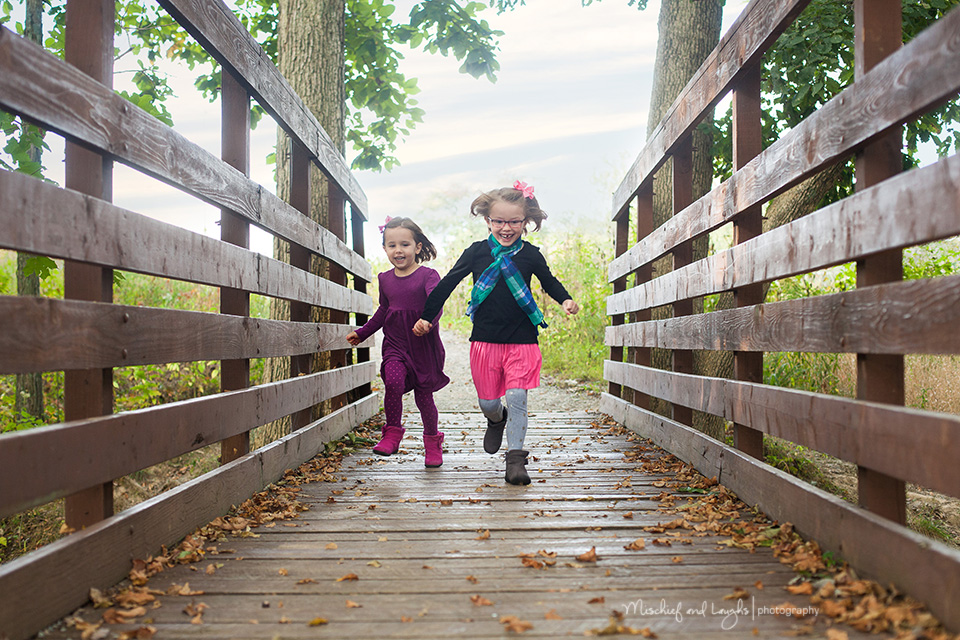Sisters running on a bridge, Mischief and Laughs Photography