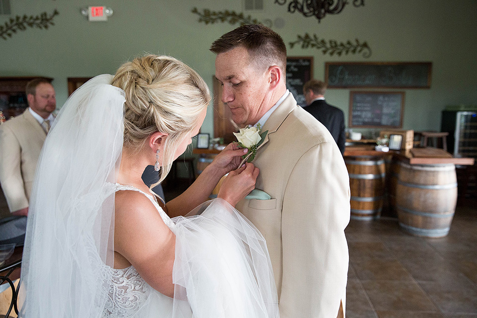 Bride puts boutonniere on groom's tux, Finger Lakes wedding photographer