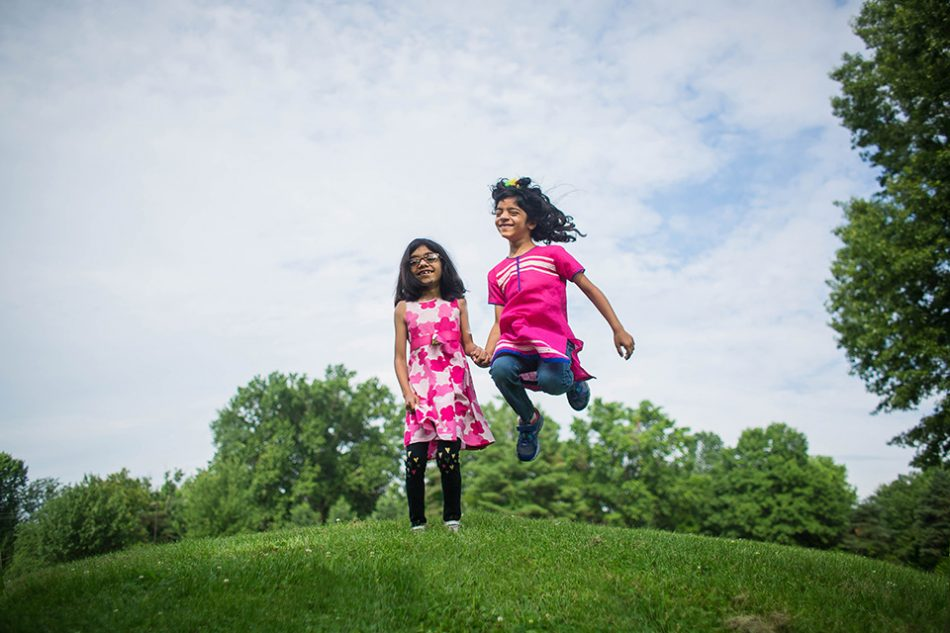 two girls jumping during their family photo session in Blue Ash