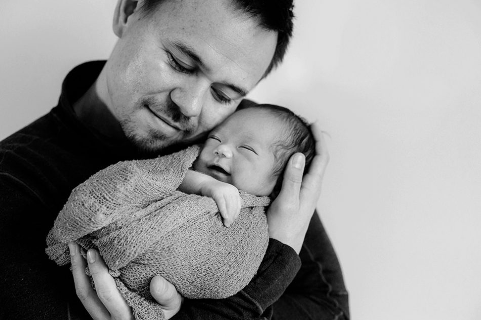 Newborn baby smiles while held by his father