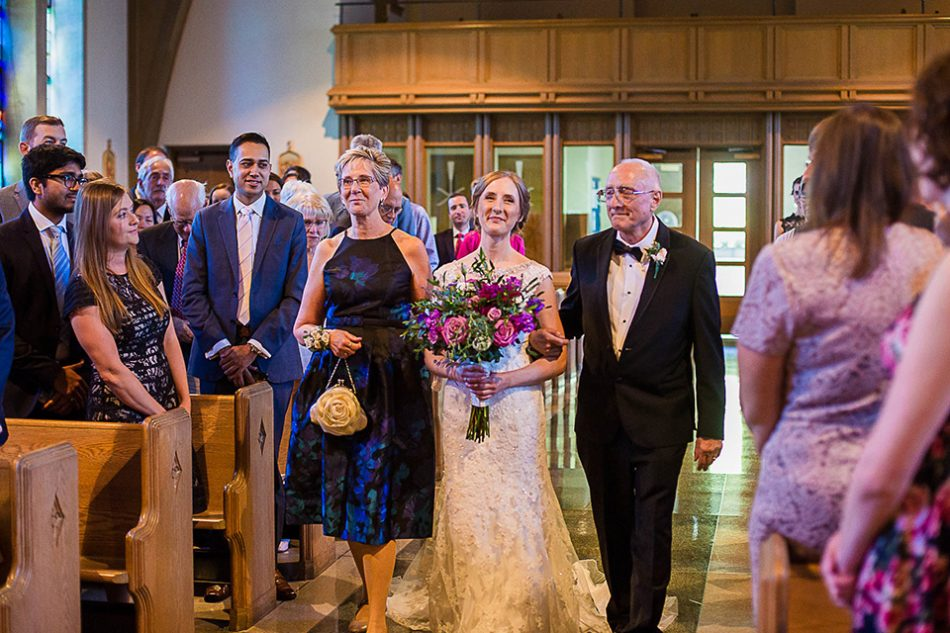 Bride with her parents walking down the aisle