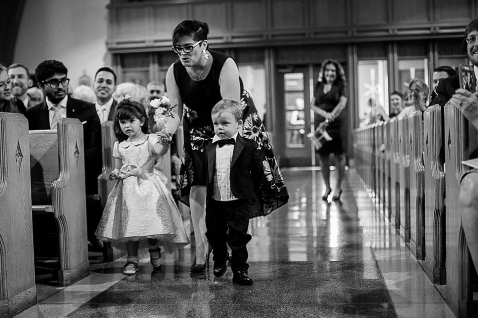 flower girl and ring bearer walk down the aisle together