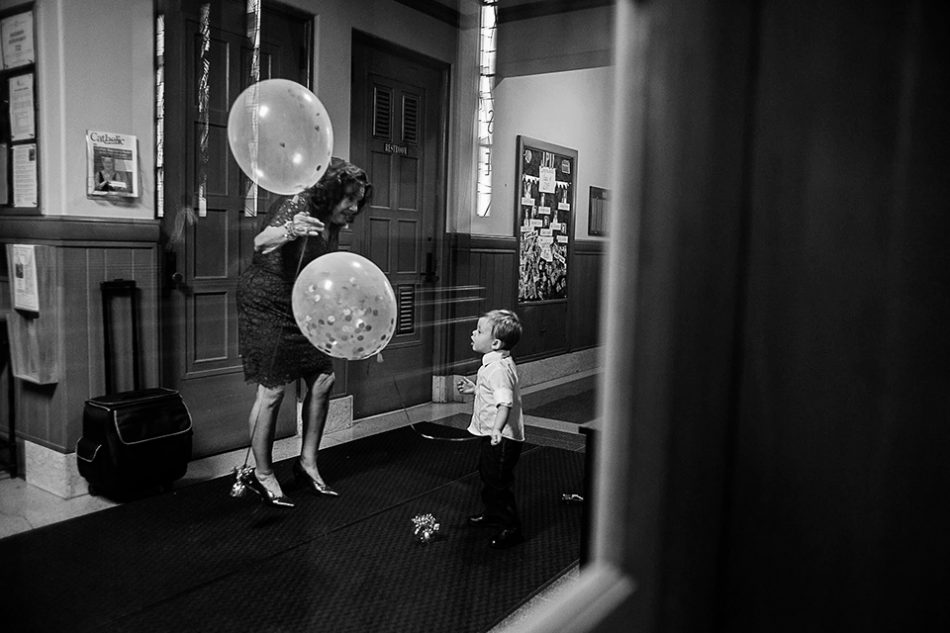 child plays with balloons during a long catholic wedding mass