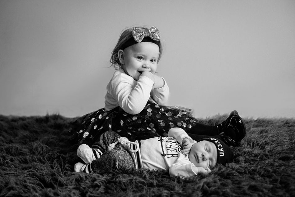 big sister poses with little brother during the newborn photo session